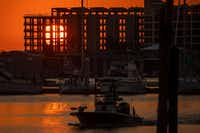The rising sun shines through the skeletal remains of the Clines Landing condominium tower as boats navigate the Dennis Dryer Municipal Harbor in Port Aransas nearly a year after Hurricane Harvey devastated the Texas Gulf Coast city.(Smiley N. Pool/Staff Photographer)