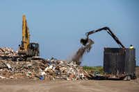 "Workers pile a new load of debris on ""Mount Trashmore,"" the pile of debris created by the post-Hurricane Harvey cleanup in the Texas Gulf Coast city of Port Aransas. (Smiley N. Pool/Staff Photographer)"