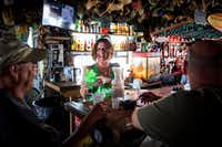 Amy Myers laughs with JP Songer (left) and Brian Underwood as she tends bar at Shorty's Place in Port Aransas. A number of businesses in the Texas Gulf Coast city remain closed, some in ruins, nearly a year after Hurricane Harvey hit.(Smiley N. Pool/Staff Photographer)