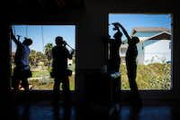 Workers replace windows on a home on South 12th Street that remains vacant nearly a year after Hurricane Harvey slammed ashore in the Texas Gulf Cost city of Port Aransas.(Smiley N. Pool/Staff Photographer)