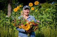 Amanda Vanhoozier of Bishop Hill Farm with a fresh bouquet of cut flowers from her Coppell garden.(Robert W. Hart/Special Contributor)