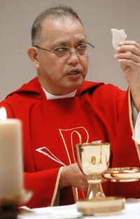 Rev. Edmundo Paredes prepares for communion during a mass in June, 2008 at St. Cecilia Catholic church, after fire destroyed the sanctuary.(Juan Garcia/The Dallas Morning News)