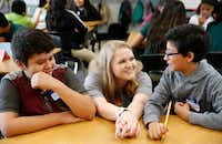 New teacher Caroline Rodgers talks with Brandon Garcia (right) as Brandon Navarr looks on during their sixth-grade class at Carolyn G. Bukhair Elementary School in Dallas on Monday. Rodgers' grandmother is Carolyn Bukhair, the school's namesake.(Vernon Bryant/Staff Photographer)