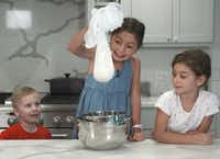 Sophie Massad holds up cheesecloth with fresh ricotta cheese she just made with her sister, Adele (right), and friend, Sam Booke.(Brian Elledge/Staff photographer)