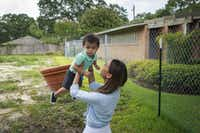 Cathy Pham plays with son Aidan at the site where their home once stood in southwest Houston. A year ago, a <i>Dallas Morning News </i>photo of their rescue went viral.(Smiley N. Pool/Staff Photographer)