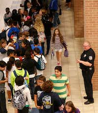 McKinney police senior resource officer Chris Golden waves at students as they make their way to the cafeteria at Scott Johnson Middle School in McKinney.(Vernon Bryant/Staff Photographer)