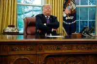 President Donald Trump crossed his arms after speaking with Mexican President Enrique Pena Nieto on the phone about a trade agreement between the United States and Mexico on Monday in the Oval Office of the White House. (Evan Vucci/The Associated Press)