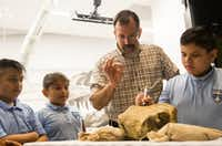 Under the supervision of paleontologist Ron Tykoski, Angel Perez (from left), 10, Enely Torres, 10, and Rafael Fernandez, 9, try their hand at removing stone from a fossil during a ribbon cutting for the new Paleo Lab in the T. Boone Pickens Life Then and Now Hall of the Perot Museum of Nature and Science on Tuesday. Sitting behind a large glass window, the new permanent exhibit offers visitors real-time views as workers process and prepare fossils.(Ryan Michalesko/Staff Photographer)