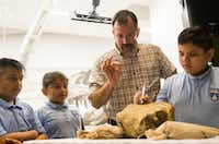 Under the supervision of paleontologist Ron Tykoski,  Angel Perez (from left), 10, Enely Torres, 10, and Rafael Fernandez, 9, try their hand at removing stone from a fossil during a ribbon cutting for the new Paleo Lab in the T. Boone Pickens Life Then and Now Hall of the Perot Museum of Nature and Science on Tuesday. Sitting behind a large glass window, the new permanent exhibit offers visitors real-time views as workers process and prepare fossils.  (Ryan Michalesko/Staff Photographer)