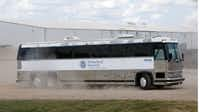 A Homeland Security bus carries detained employees away after the raid at Load Trail.(Nathan Hunsinger/Staff Photographer)