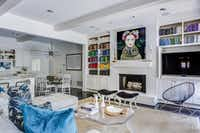 Emily Larkin makes artwork — and not the TV screen — the focal point by placing the screen off-center in a cabinet, that also helps corral all the cords and components.(EJ Interiors)
