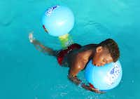 King Horton, 10, of Dallas, takes a moment to rest on an inflatable at the Bonnie View swimming pool in Dallas on July 22, 2018. (Carly Geraci/Staff Photographer)