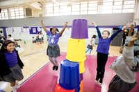 From left: Kayla Quiroga, 8; Ny'Angela Carrathus, 8; Caroline Fenlaw, 9; and Justice MacDonald, 8, celebrate after building a pyramid out of plastic buckets during a sport stacking event on Nov. 9, 2017, at Solar Preparatory School for Girls at James B. Bonham in Dallas. (Jeffrey McWhorter/Special Contributor)