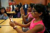 Sixth-graders Sachi Thakkar (right foreground), 11, and Aakanksha Gorla (center), 11, look for the STOP!t mobile application during a presentation at Lawler Middle School in Frisco on Wednesday. The mobile app encourages students to report suspicious behavior and threats. (Vernon Bryant/Staff Photographer)