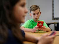 "Sixth-graders Brock Benner (right), 11, and Lauren Bazan (foreground left), 11, look for the STOP!t app. Frisco ISD is also launching a new campaign called ""Your Words Matter"" to educate students about the consequences of what they say or post online.(Vernon Bryant/Staff Photographer)"
