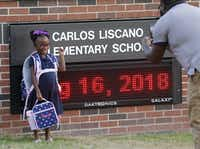 Kindergartner Bayleigh Briggs gets her photo taken by her dad, Chris Briggs, in front of the school sign on the first day of school at Carlos Liscano Elementary School in Frisco on Aug. 16, 2018.(Vernon Bryant/Staff Photographer)