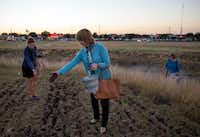 "Mary Ruehle and Ann Willet toss their ""seed bombs"" into a field as Frances Jones joins them following a class on seed saving at the Texas A&M AgriLife Research and Extension Center.(G.J. McCarthy/File 2016)"
