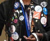 Adrianne George of Democrats Abroad wears pins at the Democratic National Committee's summer meeting, Thursday, Aug. 23, 2018, in Chicago. (Annie Rice/The Associated Press)