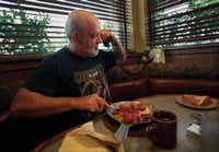 """Trucker Joe '""""Lucky"""" Moews eats  breakfast while talking on the telephone to his wife, Nancy, at  the Flying J Truck Stop.(File Photo/Staff)"""