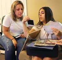 Daisy Serrano-Dominguez (right) looks at family photos with Dulce Dominguez after the cousins found each other through Facebook. The connection they made helped police solve a 1996 murder.(Louis DeLuca/Staff Photographer)