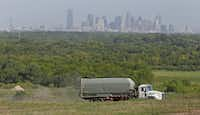 With the downtown Dallas skyline in the background, a trucks makes its way along the road in the McCommas Bluff Landfill at 5100 Youngblood Road in Dallas on Thursday, Aug. 16, 2018.(Louis DeLuca/Staff Photographer)