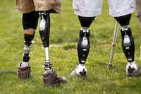 The prosthetic legs of Dana Bowman (left), U.S. Army retired sergeant first class and CEO of the HALO for Freedom Warrior Foundation, are seen alongside a fellow injured soldier (not named) after a skydive jump over Texas Motor Speedway on March 1, 2013.(File Photo/Tom Fox)