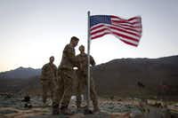 "<p><span style=""font-size: 1em; background-color: transparent;"">Capt. Erik Schutz, 26, and Capt. Matt Schachman, 28, raise a new American flag to commemorate the 10th anniversary of the 9/11 attacks as Capt. Ron Hopkins, 27, looks on at Forward Operating Base Bostick in Kunar province, Afghanistan.</span></p>(2011 File Photo/The Associated Press)"
