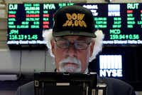 "Stock markets proved resilient after the crisis, with the Dow Jones Index reaching record levels. Trader Peter Tuchman displays the market's optimism with a ""Dow 26,000"" hat as he works on the floor of the New York Stock Exchange. (File Photo/The Associated Press)"