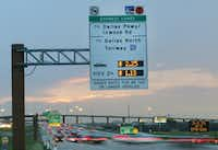 Tollway signs post the cost for travelers on the eastbound lane of LBJ. Under a plan unveiled Thursday, the toll lane discount for vehicles with two or more occupants will be replaced with a reward system.(2016 File Photo/Staff)
