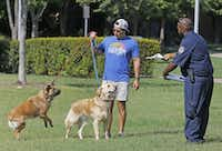 Dallas Animal Services field officer Allen Davis (right) handed out educational information about the city's  leash law Sept. 4 at Griggs Park.(Louis DeLuca/Staff Photographer)