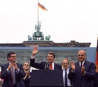 President Ronald Reagan acknowledged applause after speaking to an audience in front of the Brandenburg Gate in Berlin on June 12, 1987. Beside Reagan are the president of the German Parliament, Philipp Jenninger (left), and Germany's chancellor, Helmut Kohl (right). The 40th U.S. president served from 1981 to 1989.(Ira Schwartz/The Associated Press)