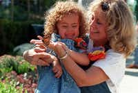 <p>Amy Powell shows her granddaughter Ashton  Powell, 4, two of the over 1.200 butterflies released at the  Dallas Arboretum in October, 1997. (Staff Photo)</p>