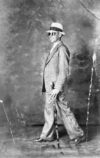 A photo of Plennie Wingo, taken in April 1931, in Dallas, shows him walking backward wearing his mirrored rearview sunglasses, which helped him navigate. He is featured in the book<i> The Man Who Walked Backward: An American Dreamer's Search for Meaning in the Great Depression</i>, by Ben Montgomery.(Pat Lefors Dawson/Little, Brown)