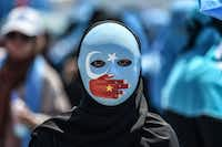 """<p><span style=""""font-size: 1em; background-color: transparent;"""">A demonstrator wearing a mask painted with the colors of the flag of East Turkestan and a hand bearing the colours of the Chinese flag attends a protest denouncing China's treatment of ethnic Uighur Muslims during a deadly riot in July 2009 in Urumqi, in front of the Chinese consulate in Istanbul, on July 5.</span></p>(Ozan Kose/Agence France-Presse)"""