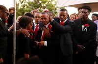 Allison (hidden) and Bertrum Jean hug as they surrounded by family and friends as their son Botham Shem Jean is buried at Choc Cemetery in Castries, St. Lucia Sept. 24, 2018. Jean was shot and killed in his apartment by off duty Dallas police officer Amber Guyger. Guyger was fired the same day Jean was buried in the cemetery overlooking the Caribbean Sea.(Vernon Bryant/Staff Photographer)