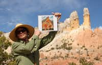 Ghost Ranch tour guide Karen Butts holds up a copy of Georgia O'Keeffe's <i>The Cliff Chimneys, 1938&nbsp;</i>&nbsp;during a tour of the places the artist painted at Ghost Ranch.(2010 File Photo/The Associated Press)