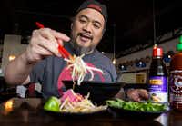 Owner Khanh Nguyen of Dalat Restaurant adds sprouts to his pho.(Carly Geraci/Staff Photographer)
