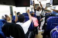 In this Aug. 24, 2018 photo, Black Voters Matter Fund co-founders, LaTosha Brown, left, and Cliff Albright, right, lead Mississippi grassroots partners in some empowerment cheers aboard a bus tour to Greenville, Miss. Brown said the time is now for black women to lead again. The Mississippi Delta was part of a three-state bus tour to build interest and excitement for the upcoming election with grassroots organizations, document the campaigning in locales with important upcoming races where black turnout will be key and expose traveling national media to the work led by mostly women leaders. (Rogelio V. Solis/The Associated Press)