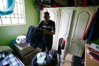Bertrum Jean sorts through clothes that Botham Jean kept in the closet of his childhood bedroom in St. Lucia. (Vernon Bryant/Staff Photographer)