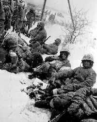 U.S. Marines, fighting their way from Chosin to Hungnam, Korea, take a rest in the snow somewhere on the route in December 1950 during the Korean War. (Associated Press)