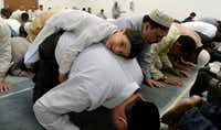 Subhan Latif, 4, rests on his father, Zubair Latif,  during a prayer service for Eid-al-Fitr, an Islamic holiday celebrating the end of Ramadan, at the Bait ul Ikram mosque in Allen on Aug. 9, 2013.(File Photo /Staff)