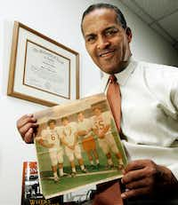 In this Dec. 16, 2005 photo, Dallas attorney and former Texas football player Julius Whittier displays a 1971 newspaper photo of himself with teammates Bruce Cannon, Greg Dahlberg, and coach Darrell Royal in Dallas. The first African-American football letterman at the University of Texas, Whittier's family later sued the NCAA on behalf of college players who suffered brain injuries.(TIM SHARP/AP)