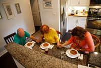 Henry Brigman, Iris Brigman and Amy Hardesty pray before dinner at the Brigman home in Frisco on Aug. 29.  Hardesty is renting a room at the Brigman home while teaching at Fisher Elementary School in Frisco.(Vernon Bryant/Staff Photographer)