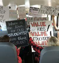 Teachers hold up their signs on a school bus as the head to the Oklahoma capitol in Oklahoma City for another day of the teacher walkout in April. (Photo submitted by Amy Hardesty)