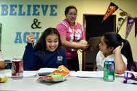 Sixth-graders Mallory Perez (left) and Valerie Perez work on their math homework as mentor Marthaelena Tramel prepares to assist them during the Trinity River Mission after-school program in West Dallas, Monday, Sept. 10, 2018.(Ben Torres/Special Contributor)