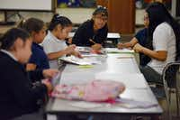 Fourth-graders Angie Zamacona (left) and Hellen Trujillo work on their math homework with tutor Karen Esquivel (far right), during the Trinity River Mission after school program in West Dallas, Monday, Sept. 10, 2018.(Ben Torres/Special Contributor)