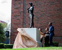 Artist Emmanuel Gillespie, right, unveils his statue of MLB Hall of Famer and Dallas native Ernie Banks on Thursday, September 20, 2018 outside Booker T. Washington High School for the Performing and Visual Arts in Dallas. (Ashley Landis/Staff Photographer)