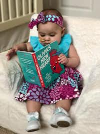 Olivia Solis at almost 8 months, with the book about her life so far(Courtesy Miguel Solis)