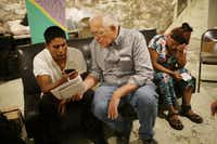 Ruben Garcia, center, director of the Annunciation House in El Paso,  speaks on a cell phone with a person from the Office of Refugee Resettlement. Garcia said shelters in West Texas and New Mexico are filled to capacity with record number of families from Central America.<br>(Joe Raedle/Getty Images)