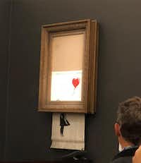 In a photo provided by Sotheby's, the moment when Banksy's <i>Girl With Balloon</i>was destroyed by a remote-control shredder, at Sotheby's. The British street artist Banksy appeared to pull off one of his most spectacular pranks(Sotheby's)